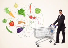 Businessman with shopping cart with vegetables. Businessman pushing a shopping cart and healthy vegetables coming out of it Stock Photos