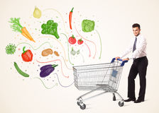 Businessman with shopping cart with vegetables. Businessman pushing a shopping cart and healthy vegetables coming out of it Stock Image