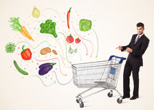 Businessman with shopping cart with vegetables. Businessman pushing a shopping cart and healthy vegetables coming out of it Royalty Free Stock Photo
