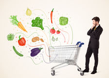 Businessman with shopping cart with vegetables. Businessman pushing a shopping cart and healthy vegetables coming out of it Royalty Free Stock Photography