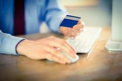 Businessman shopping online at desk Stock Photos