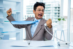 Businessman shouting as he holds out phone. In office Royalty Free Stock Photo