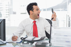Businessman shouting as he holds out phone at office Royalty Free Stock Photos