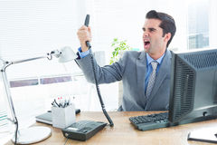Businessman shouting as he holds out phone at office Royalty Free Stock Images