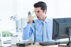 Businessman shouting as he holds out phone at office Royalty Free Stock Image