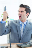 Businessman shouting as he holds out phone at office Stock Photo