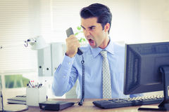 Businessman shouting as he holds out phone at office Royalty Free Stock Photo