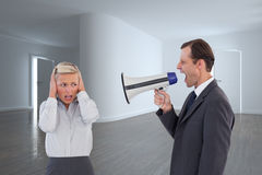 Businessman shouting at colleague with his bullhorn. Composite image of businessman shouting at colleague with his bullhorn Royalty Free Stock Photos