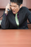 Businessman shouting down phone Stock Photography