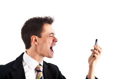 Businessman shouting at his phone. Portrait of a businessman in a funny facial expression while yelling something at the phone Stock Photos