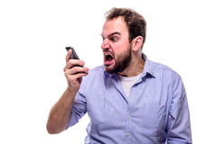 A businessman shouting into his phone. Concept of anger, aggression and stress in the workplace Royalty Free Stock Photography