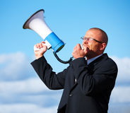 Businessman shouting in a megaphone Stock Images