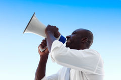 Businessman shouting in a megaphone. African businessman shouting in a megaphone Stock Photo