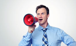 Businessman shouting into a megaphone Stock Images