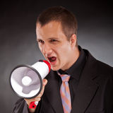 Businessman shouting through megaphone Stock Image