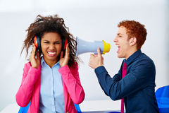 Businessman shouting megaphone to african woman Royalty Free Stock Images