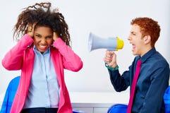 Businessman shouting megaphone to african woman Stock Photos