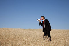 Businessman shouting at the megaphone to you. Businessman at the field shouting at the megaphone to you Royalty Free Stock Image