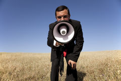 Businessman shouting at the megaphone to you. Businessman at the field shouting at the megaphone to you Stock Image
