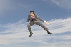 Businessman Shouting In Midair. Full length of a businessman in midair shouting against cloudy sky Royalty Free Stock Images