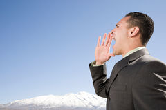 Businessman shouting by mountains Stock Image