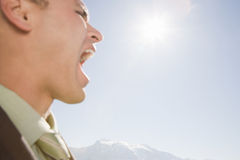 Businessman shouting by mountains Royalty Free Stock Images