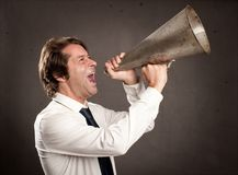 Businessman shouting with an old megaphone. On a gray background Royalty Free Stock Photography