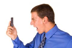 Businessman shouting at phone. A young, caucation/white businessman, well lit in blue long sleeve shirt with tie. Facing left. Lifting up right hand with cell Royalty Free Stock Photo