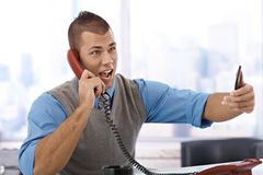 Businessman shouting on phone. Angry young businessman shouting on landline phone in office, holding mobile phone Royalty Free Stock Photography