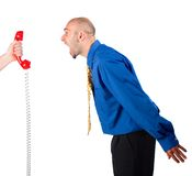 Businessman Shouting at Phone. Businessman shouting out red phone receiver, which is being held by another person Stock Photos
