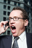 Businessman shouting into phone Royalty Free Stock Photography