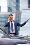 Businessman shouting into the phone. Near the car and on the background of office Stock Photos