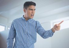 Businessman shouting and pointing angrily in minimal room Royalty Free Stock Photo