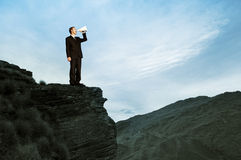 Businessman Shouting on the Top of the Mountain Stock Photo