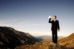 Businessman Shouting on the Top of the Mountain Stock Photography