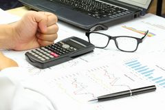 Businessman show hand boot power and Summary report. Finance capital market with calculate about cost at table office office Stock Images