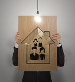 Businessman show hand draw family and house. On wooden poster as insurance concept stock photography