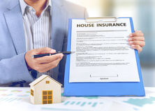 Businessman show insurance policy with wooden home model Stock Images