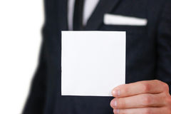 Businessman show square white paper, closeup. Showing blank flyer brochure booklet. Pamphlet hold hands. Show clear offset paper. Sheet template. Man in a royalty free stock photography