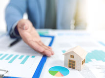 Businessman show wooden home model and business graph Stock Photo