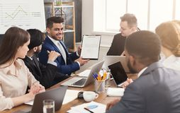 Businessman showing annual report to his colleagues. Cheerful businessman showing annual report graph to his colleagues at corporate meeting, cheering for Stock Photo