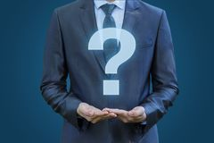 Businessman showing a bigger question mark . Businessman showing a bigger question mark on a blue background. The answers to the questions Stock Photography