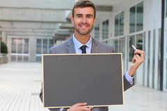 Businessman showing a blackboard with space for copy Stock Photos