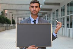 Businessman showing a blackboard with space for copy Royalty Free Stock Photos