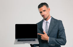 Businessman showing blank laptop computer screen Stock Images