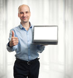 Businessman showing blank laptop computer. And thumbs up stock image