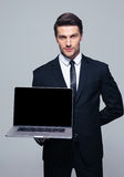 Businessman showing blank laptop screen Stock Images