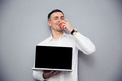 Businessman showing blank laptop screen and eating apple Stock Photos