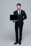Businessman showing blank laptop screen. Full length portrait of a handsome businessman showing blank laptop screen over gray background and looking at camera stock photography