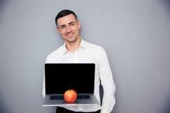 Businessman showing blank laptop screen Stock Image